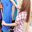 Happy young woman shopping for clothes at the mall — Stock Photo #13734131
