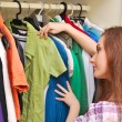 Happy young woman shopping for clothes at the mall - Stock Photo