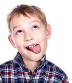Closeup portrait of a mischief boy showing his tongue — Stock Photo