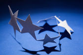 Paper stars group on a colour background — Stockfoto