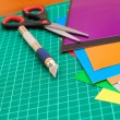 Cutting mat with paper and tools — Stock Photo
