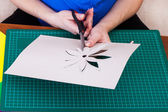 Woman's hand cutting out flower — Stock Photo