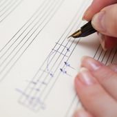 Hand with pen and music sheet — Stock fotografie