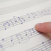 Hand with pen and music sheet — Stock Photo