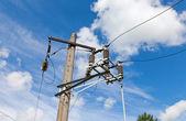 Post di energia elettrica con filo contro il luminoso cielo azzurro e nuvole — Foto Stock