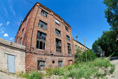 Old abandoned building against blue sky in summer day — Stock Photo