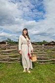 年轻妇女对古代传统俄罗斯乡村的背景 — 图库照片