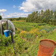 Countryside landscape with retro washstand and rusty water barre - Stock Photo