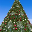 Firtree with Xmas decoration over blue sky — Stock Photo