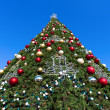 Foto Stock: Firtree with Xmas decoration over blue sky