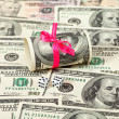US dollars wrapped by ribbon on money background - Stock Photo