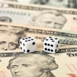 Two dice laying over a pile U.S. dollars — Stock Photo