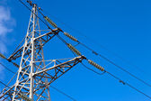 High voltage electricity pylon over blue sky — Stock Photo