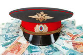 Russian police officer cap on the batch of banknotes — Stock Photo