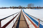 Suspension foot bridge over the frozen river — Stock Photo
