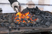 Blacksmith forges a red-hot iron in the forge — Stock Photo