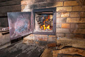 Old stove with open door and burning the wood — Stock Photo