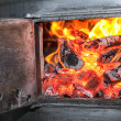 Old stove with open door and burning the wood — Stock Photo #27130697