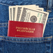 Stock Photo: Russian passport and dollar bills in the back jeans pocket