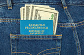 Kazakhstan passport and dollar bills in the back jeans pocket — Stock Photo