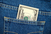 Five dollar bill in the back jeans pocket — Stock Photo