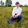 Young woman gathers cranberries in a swamp — Stock Photo