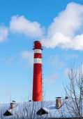 Red factory chimney against blue sky in winter — Stock Photo