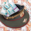 Stock Photo: Stack of bundled russiruble banknotes in officer's cap