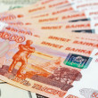 Stock Photo: Russiroubles bills laying over dollars background