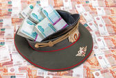 Stack of bundled russian ruble banknotes in the officer's cap — Stock Photo