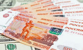 Russian roubles bills laying over dollars background — Stock Photo