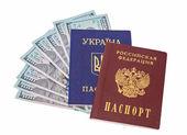 Ukrainian, Russian passports and  dollar bills over white backgr — Stock Photo