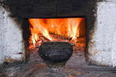 Old russian stove with iron pot and burning firewood — Stockfoto