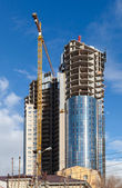 Tall buildings under construction with cranes against a blue sky — Stock Photo