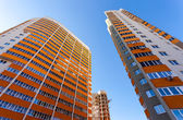 Tall apartment buildings on blue sky background — Stock Photo