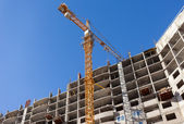 Tall buildings under construction with crane against a blue sky — Stock Photo
