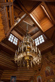 Electric chandelier in the wooden church — Stock Photo