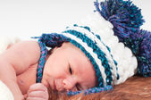 Newborn baby in knitted hat with pom-pons — Stock Photo