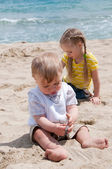 Little girl with brother sitting on the beach — Stock Photo