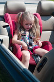 Little cute girl sitting in car seat — Stock Photo
