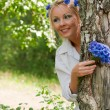 Woman looking out from behind a tree — Stock Photo