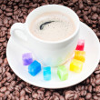 Multicolored slabs of shugar and cup of coffee — Stock Photo