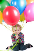 Little girl with multicolored air balloons sitting — Stock Photo