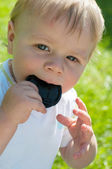 Cute baby boy holding lens cover on his mouth — Stock Photo