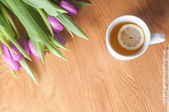 Violet tulips on the wood and tea, top view — Stock Photo