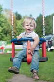 Swinging little boy in denim — Stock Photo