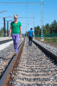 Handsome man walking on train tracks — Stockfoto