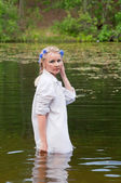 Beautiful woman in white standing in pond — Stock Photo