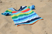 Multicolored child t-shirt on the sand — Stock Photo