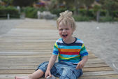 Flashy boy sits on a wooden walkway on the beach — Stock Photo